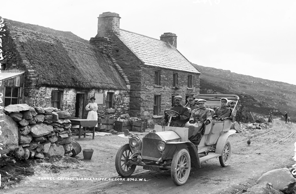 From our Lawrence Cabinet photographs - Tourists motoring past Long Tunnel Cottage, Glengariff, Co. Cork, circa 1906/07. NLI ref. LCAB 08742